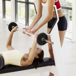 side profile of a female instructor helping a young woman exercise with weights